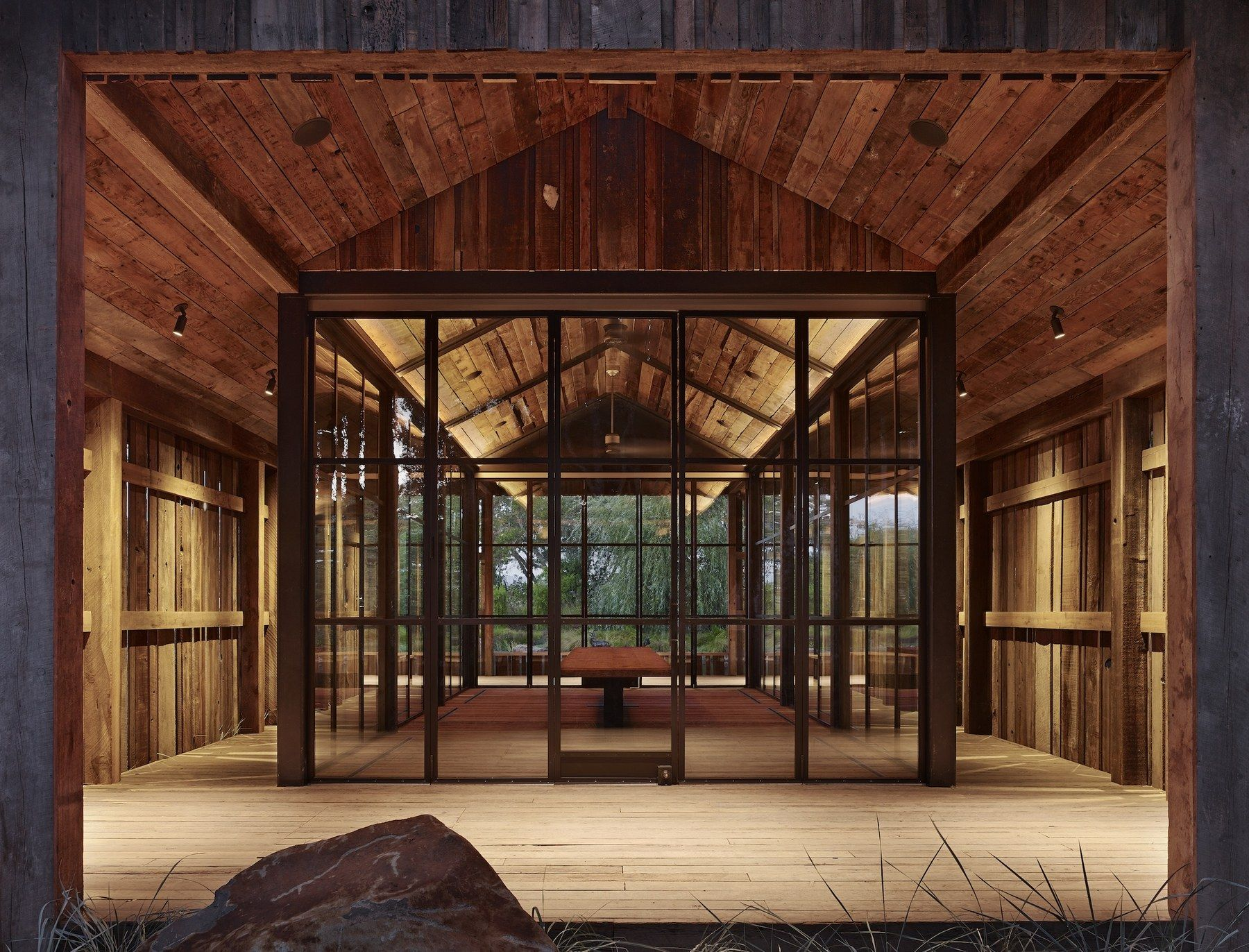 An Enclosed Glass Dining Area Stands Within This Wood Structure