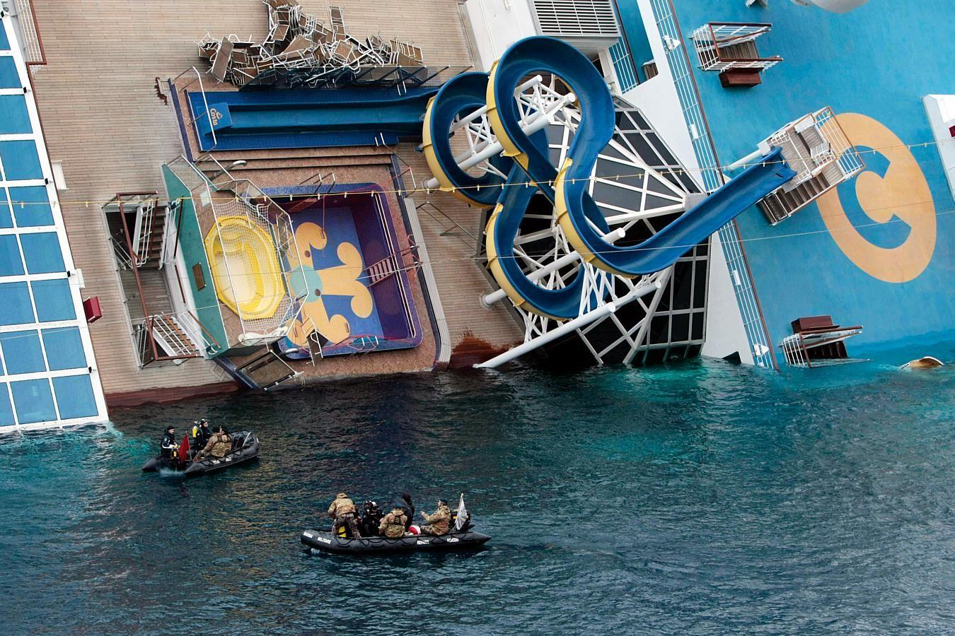 Italian Navy scuba divers approach the cruise ship Costa Concordia ...