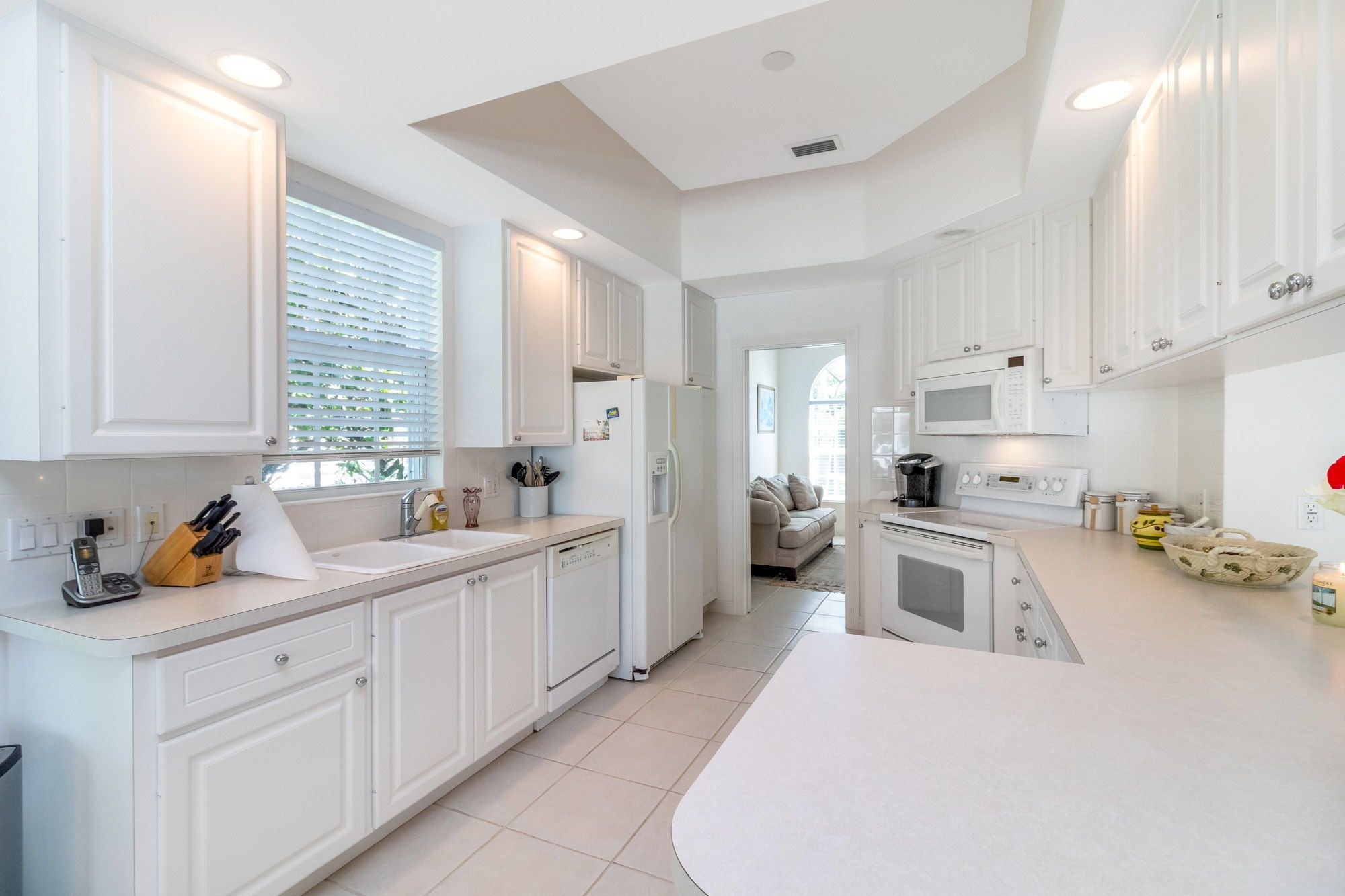 The Kitchen Is Open Concept And Has Spacious White Cabinets And Appliances A Tray Ceiling Large Behind Kitchen Design Open Concept Kitchen Palm Beach Gardens