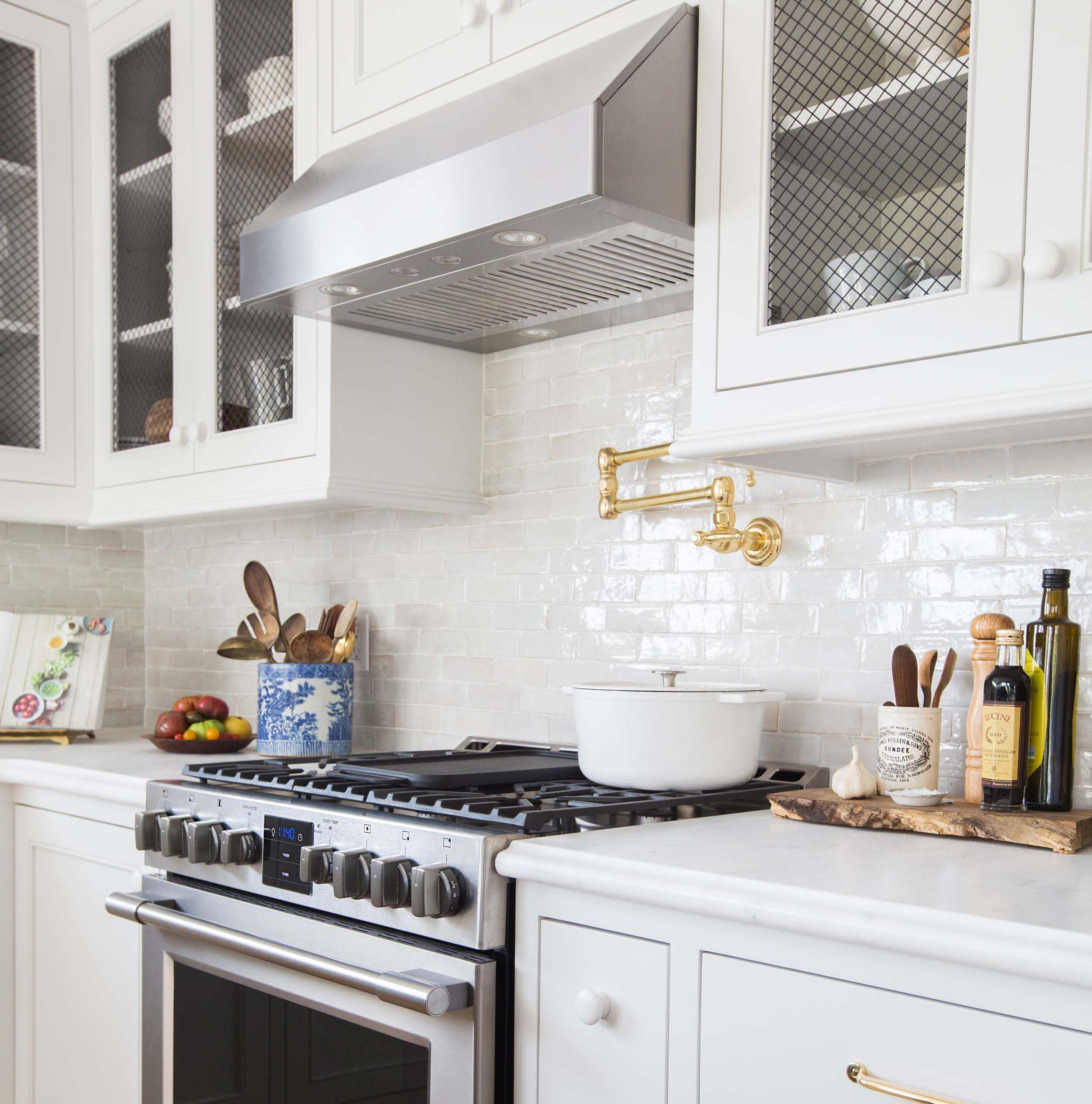 A stainless steel kitchen hood flanked by chicken wire cabinets stands over a glossy white linear tiled backsplash accented with an antique brass