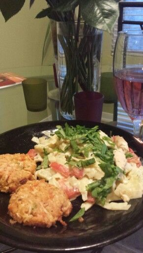 Alfredo pasta with tomatoes topped with spinach and a side of crab cakes.