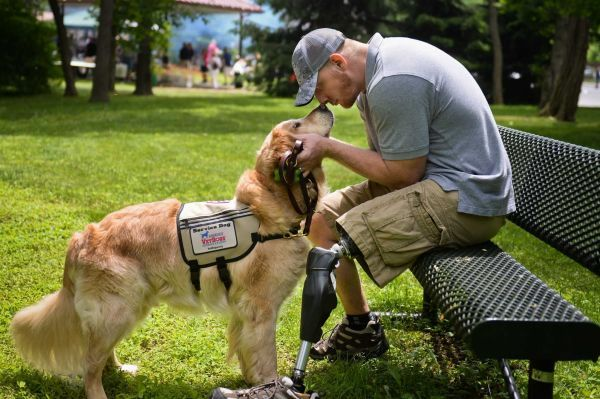 Navy Corpsman veteran Joe Worley, of Georgia, who lost his leg during the battle of Fallujah, Iraq in 2004, touches nose to nose with his service dog, Benjamin, while sitting on a bench in Smithtown, Saturday, June 6, 2015. (Credit: Steve Pfost)
