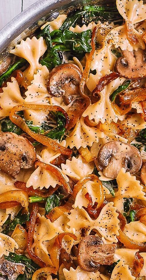 Creamy Farfalle Pasta with Spinach, Mushrooms, and Caramelized Onions.  This simple meatless Italian dinner is pure comfort food!  The bow-tie shaped pasta is perfectly matched with rich and buttery Parmesan sauce! #farfalle #pasta #bowtie #creamyfarfalle #creamypasta #creamybowtiepasta #Spinachpasta #mushroompasta #spinach #mushrooms