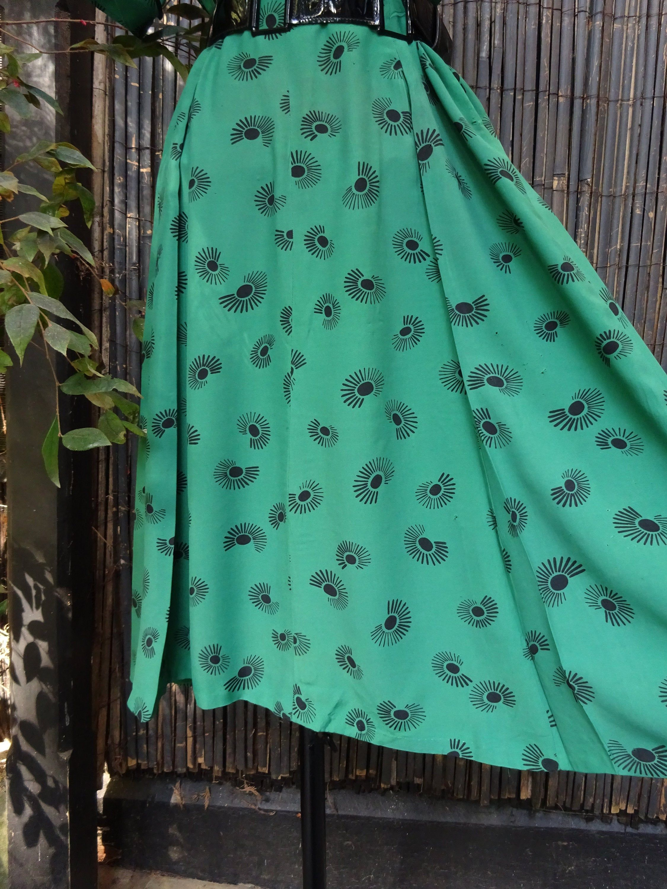 """""""This is a very Vivid coloured Kelly Green 1940s Rayon Day Dress. The design is like an eye with lashes! or a sun burst! The design is quite Art Deco. It has an edging round the neckline, cuffs and faux pockets which is a shiny ribbon. There are 4 original buttons down the front and it has a side placket with a zipper(eclair). It has 2 pleats at the back of the skirt. It is shown cinched in with a patent belt which is not included in the sale. Measurements;- Bust up 38\"""" to 40\"""" Waist up to 34\"""""""