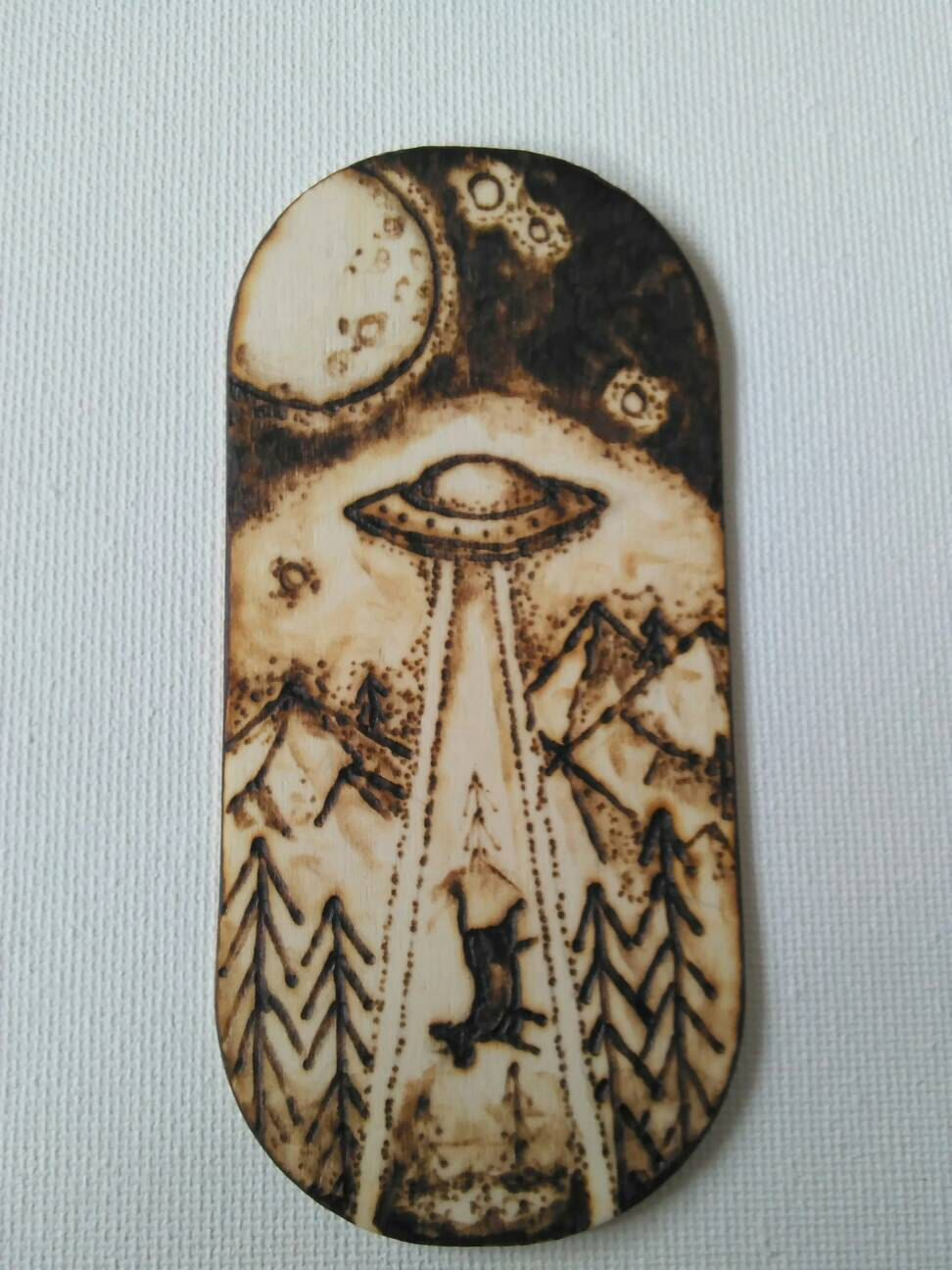 A personal favorite from my Etsy shop https://www.etsy.com/listing/266924975/alien-abduction-wood-burned-magnet