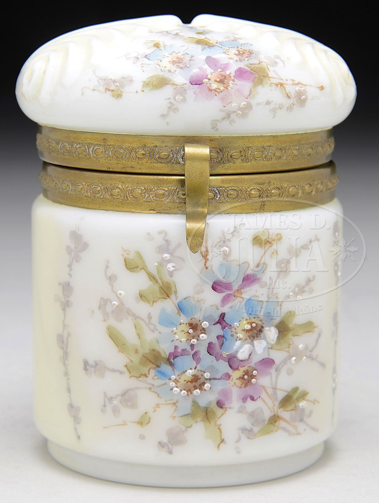 """James D. Julia, Inc. -  Wave Crest Cigarette Jar. Jar is decorated with a shell pattern molded into lid and is enameled with floral sprays having blue, purple and white flowers with green foliage. The word """"Cigarettes"""" is also enameled to the backside of jar."""