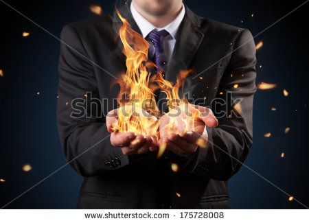 Businessman with fire in hands. Concept of threats and manager responsibility - stock photo