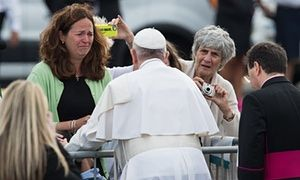 A woman cries as Pope Francis blesses her disabled son upon arrival in Philadelphia.