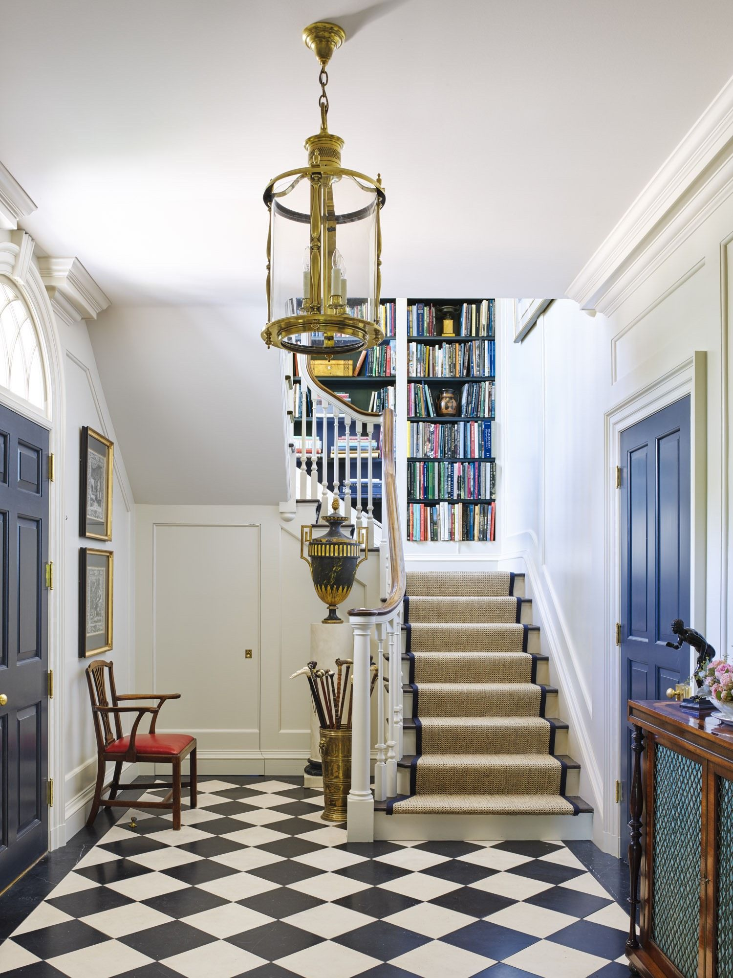 Small Entry Hall With Bookshelves Up The Stairs.