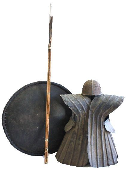 Unique set of sheet metal armor used by natives on the Indonesian island of Nias. Armored vest, hinged down the back, with a ridge of spiked sheet metal down the spine. Thin handmade armor was used to repel enemy arrows during the many civil wars fought amongst the islands inhabitants. Also included is a matching metal helmet, water buffalo hide shield, bundle of arrows, and one other tribal implement. Armor measures 24 inches wide, and 26 high, and shield is 32 inches in diameter.