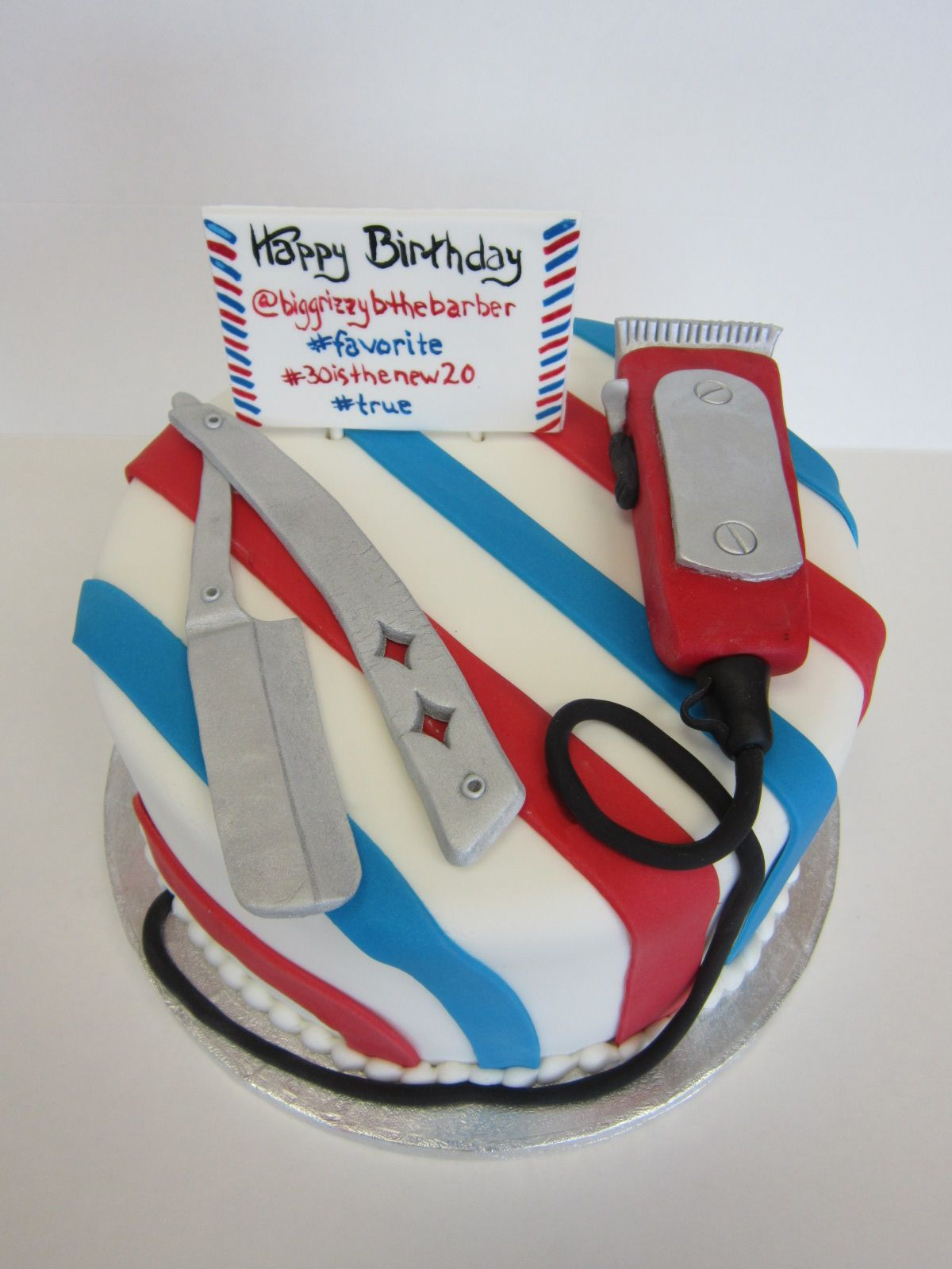 What do you give a barber for his birthday? Well a cake with all the trimmings off course! This cake is fondant covered with the red and blue barber stripes. Razor, trimmer and biz card are also edible fondant creations. This cake made by www.americandreamcakes.com (Recreation of idea from Pinterest brought in by client)