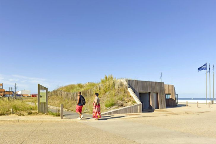 Dune Habitee is a new watersport base near the town of Saint-Hilaire-de-Riez in France that virtually disappears under a grassy dune. All but invisible under sand and grass and cleverly hidden behind wooden planks, the ocean shop is a clever and thoughtful addition to the pristine environment. Designed by Paris-based THE Architectes, Dune Habitee is built from reinforced concrete, durable hardwoods and features brilliant skylight shafts buried into the sand to bring light into the…