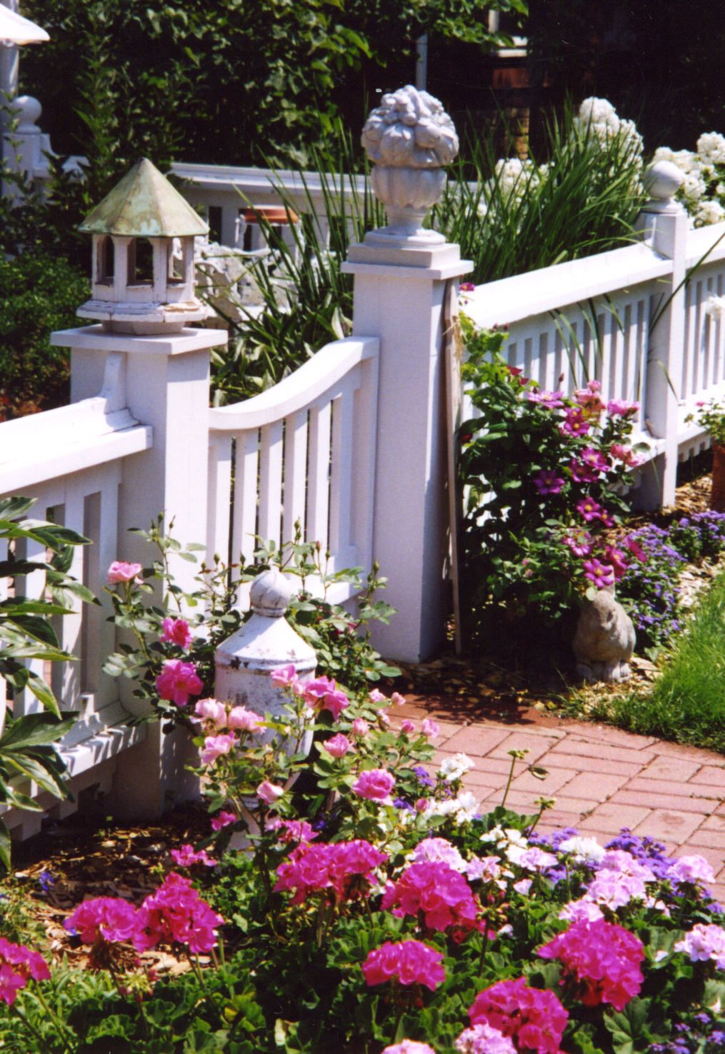 cottage fence and flowers brick path finials birdhouse on backyard fence landscaping id=94896