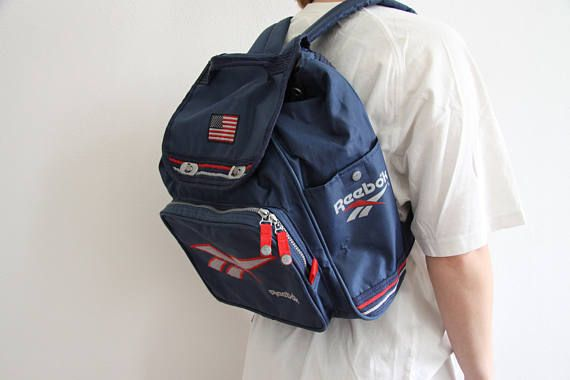 Super nice vintage backpack from Reebok in blue with USA flag. The model is  165 cm and waring a regular sized backpack.