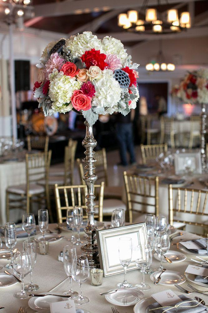 Tall wedding centerpiece. Silver pedestal. Coral, orange