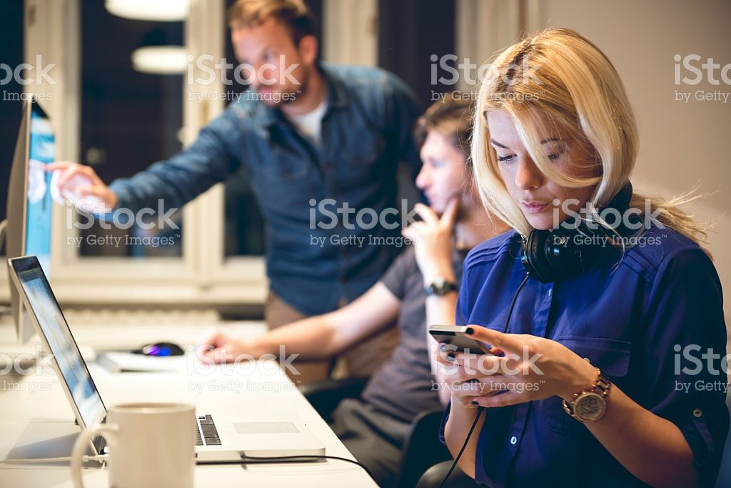 Young female designer texting on smart phone in office