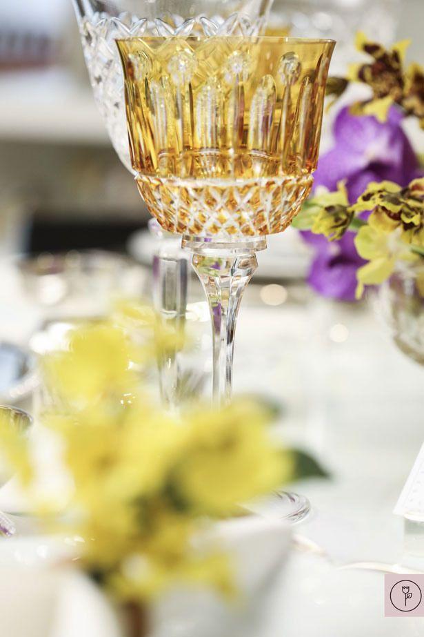 Além do colorido das orquídeas, incluímos alguns pontos de cor adicionais na mesa usando taças de cristal amarelo e porta-guardanapos de orquídea chuva de ouro. Todos os outros itens foram neutros e muito fáceis de combinar: taças para água em cristal transparente, louça Limoges branca que eu amo sobre sousplats, marcadores de lugar e descansos de talher em prata, jogos americanos e guardanapos crus e potinhos em prata para os lencinhos de limpeza – uma nova mania nossa para mimar os…