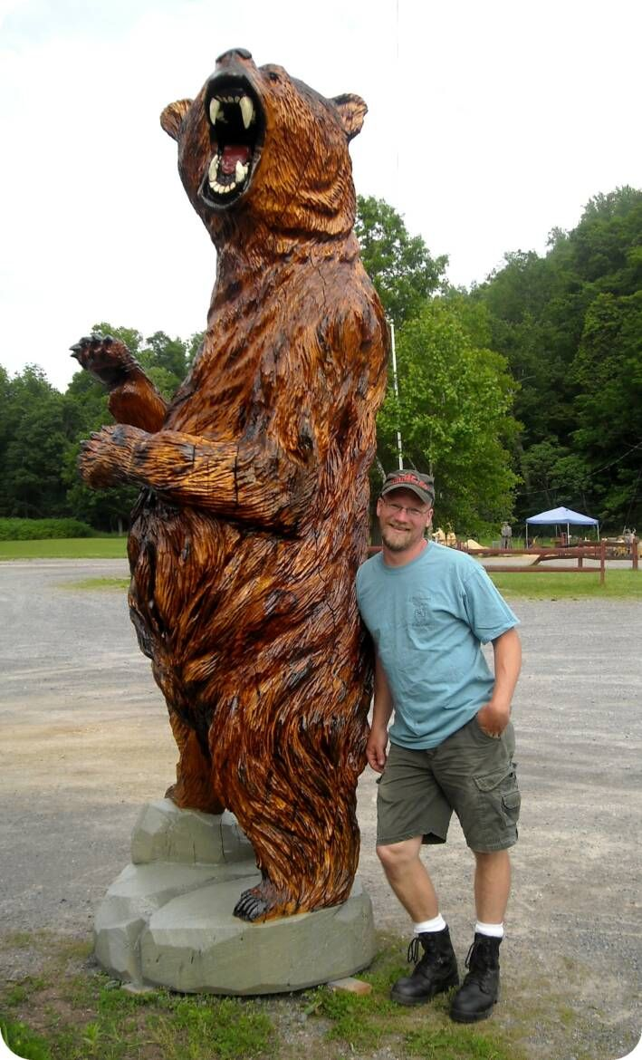 Chainsaw carved grizzly bear and artist heath bender of hb