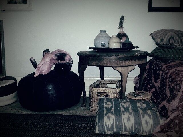 Ram skull on moroccon pouffe with pottery.