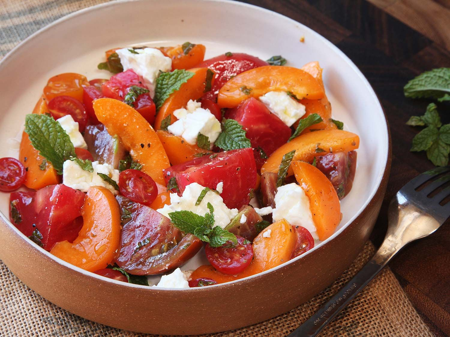 It's tough to improve on a classic Caprese salad of ripe summer tomatoes, fresh mozzarella cheese, basil, and olive oil, but it's pretty darn easy to make a nice lateral transition to something that's not quite as classic yet equally tasty. Here, I've combined those same tomatoes with sweet apricots (another of summer's treats), briny feta cheese, and mint for a take that's just as refreshing, but with a completely different personality.