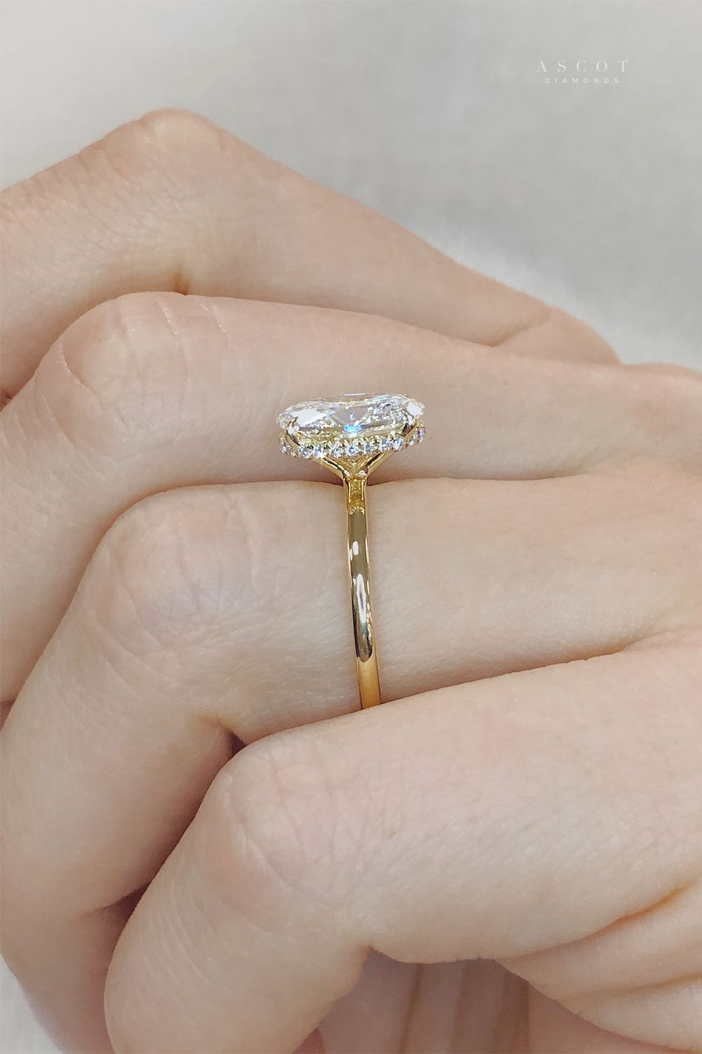 This elegant custom engagement ring features a delicate hidden halo of diamonds that wraps around the center stone.  Schedule a consultation to learn more about designing this diamond ring style.  #ascotdiamonds #engagementrings