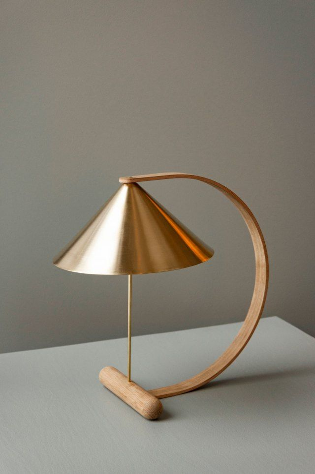 The Spenn table lamp by design studio Noidoi. Made from form-pressed oak veneer and brass, with a focused, downward-facing light, the lamp marks its designers' attempt to capture a moment of tension between two points, and the object's sculptural expression resembles a tensed arc. The look of the lamp is clean and minimalistic, with the wood as a soft and tactile counterweight.