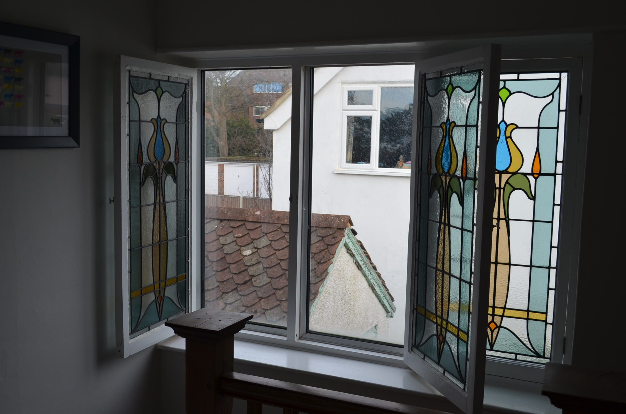 original 1920s stained glass window with double glazed installation, the original window was removed and restored and rebuilt inside the house behind a modern UPVC unit, the stained glass units open for cleaning