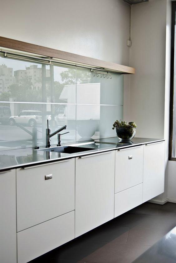Cocina con muebles blancos y encimera de acero inoxidable ...