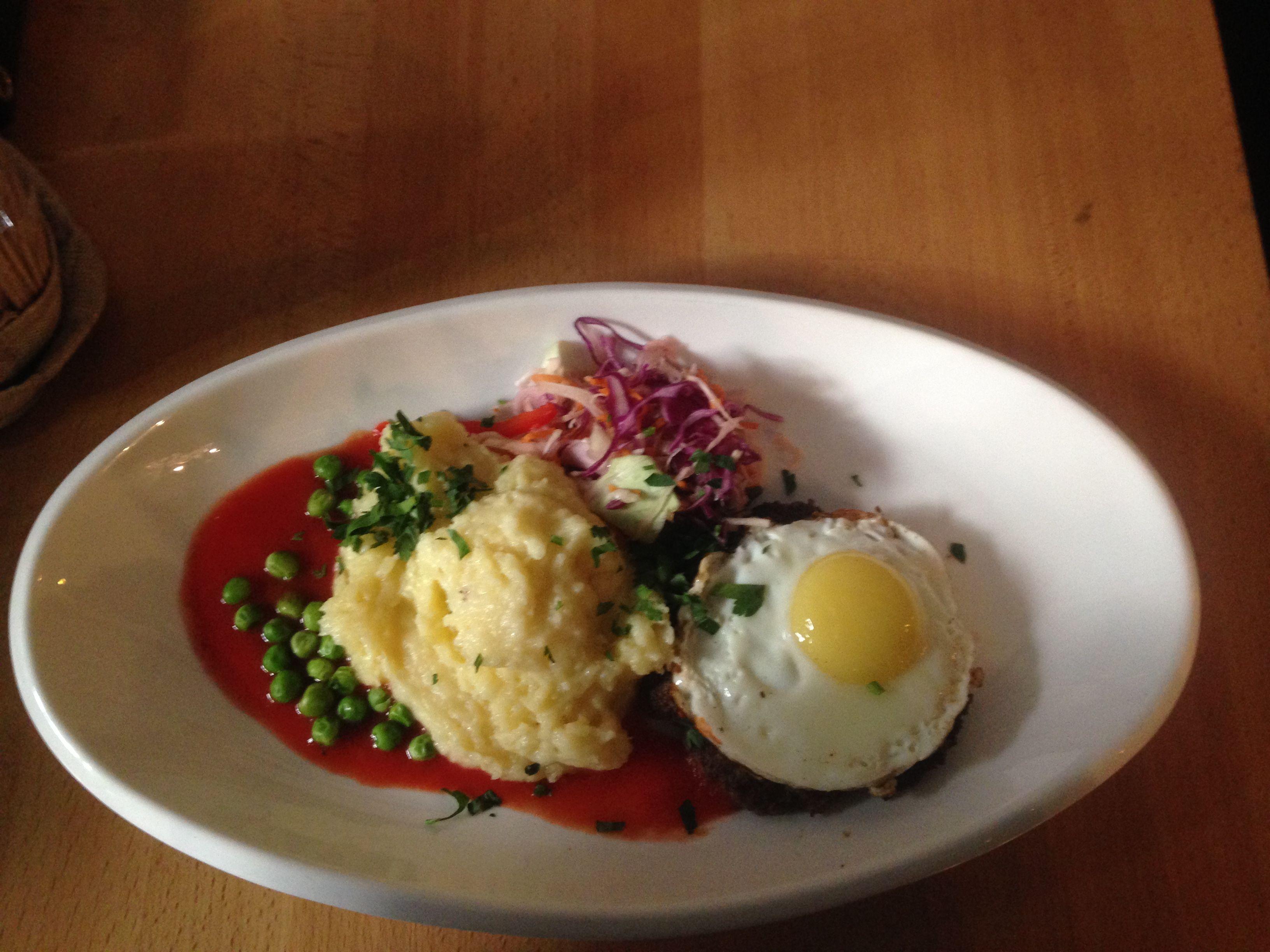 Бифштекс из рубленной говядины с яйцом и зеленым горошком и картофельным пюре кафе общество чистых тарелок