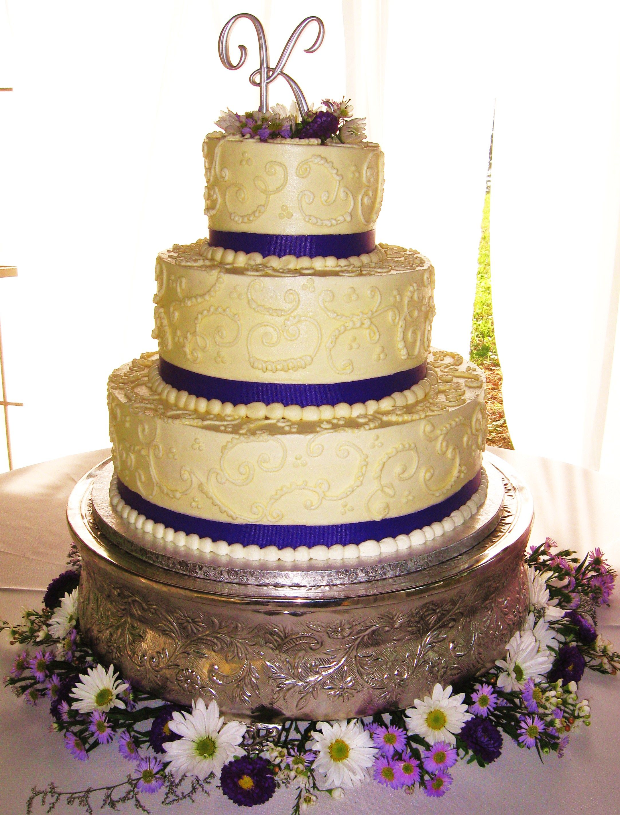3-tiered wedding cake with all white scrollwork and purple ribbon ...