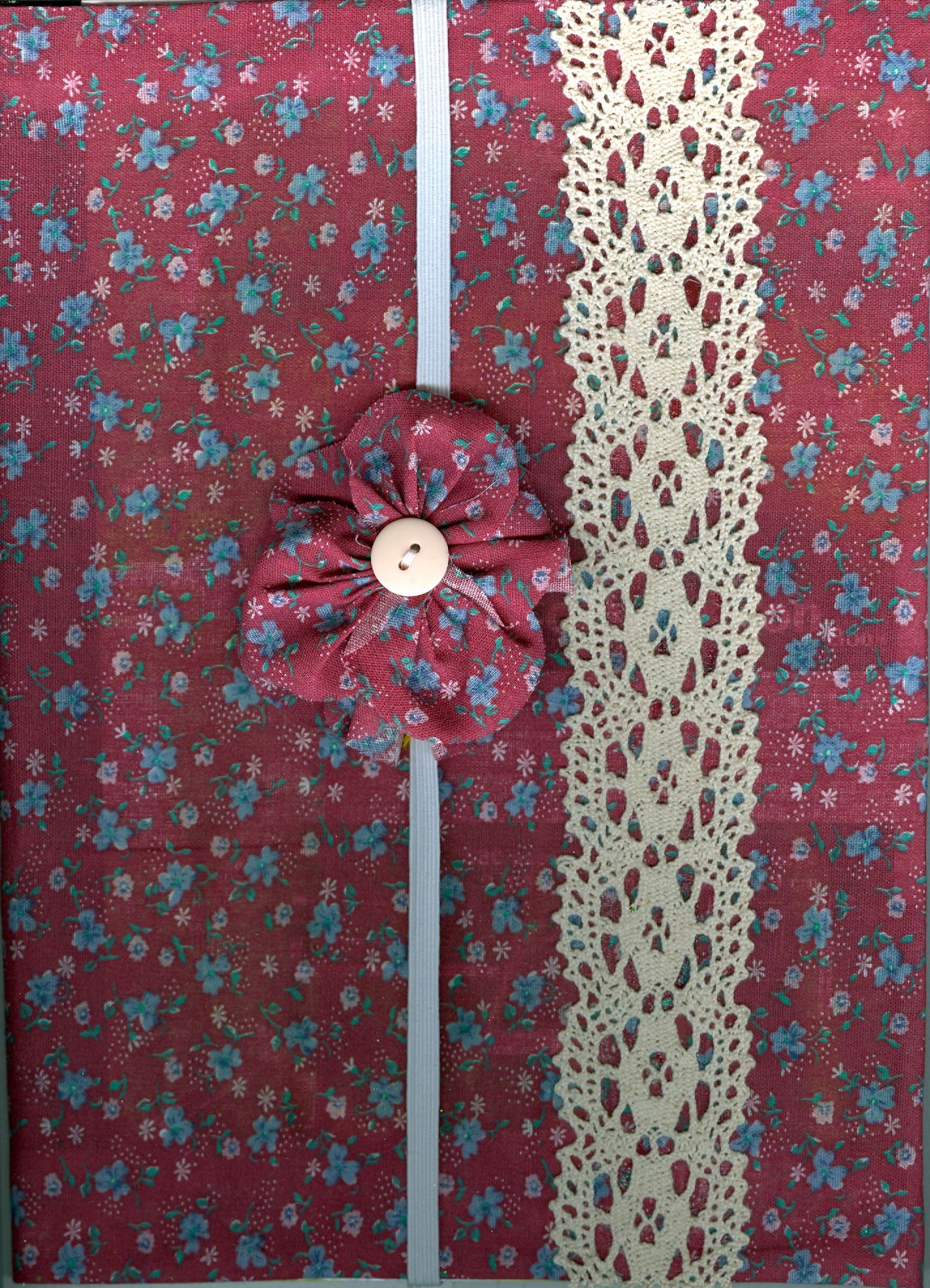 Cloth covered journal with embellished bookmark. Material was carefully glued to the cardboard cover of a dollar store bound lined book.  The elastic bookmark was decorated with a gathered piece of the same material and sewn on with a button on both sides of the flower.