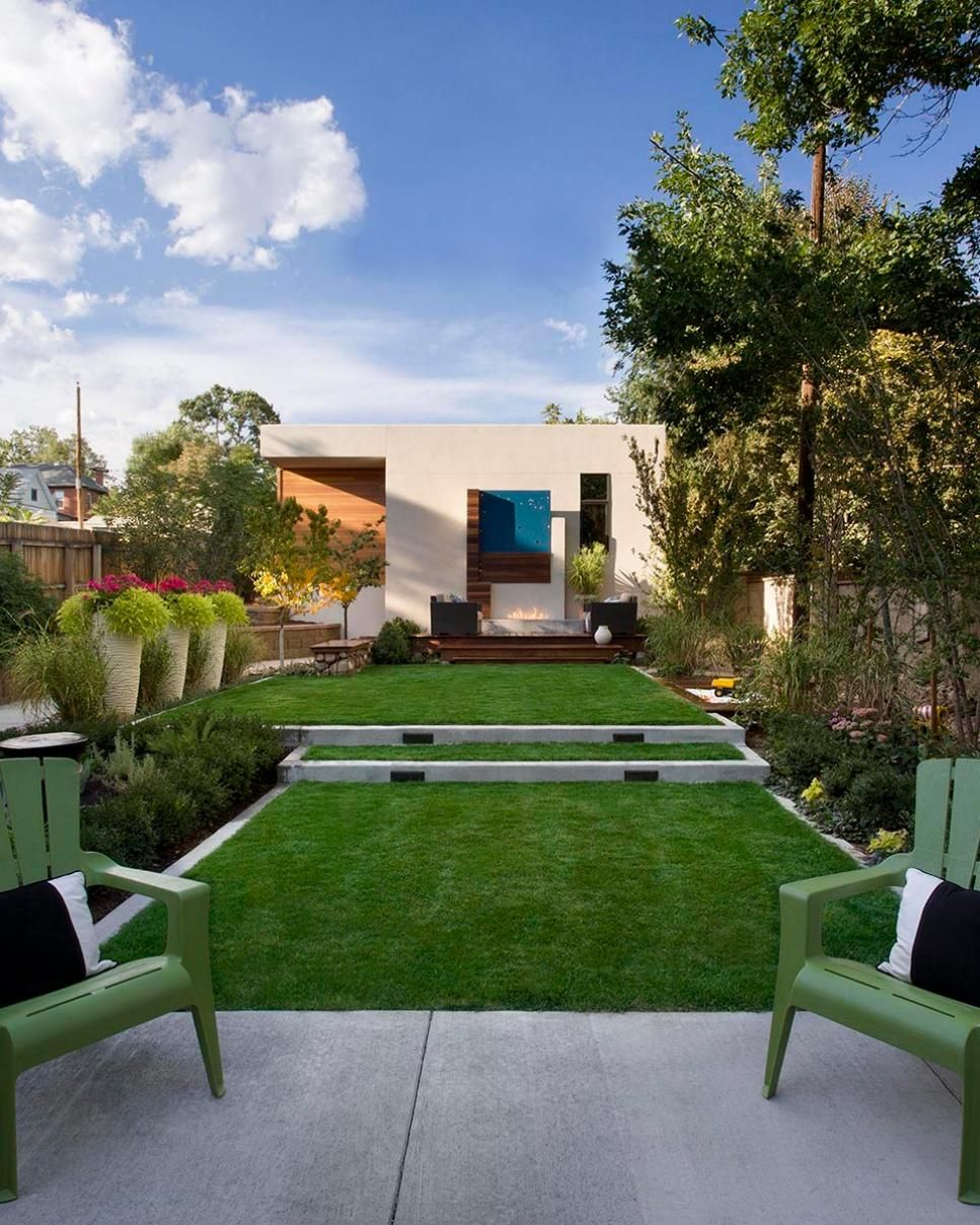 This small-ish but gorgeous back yard has a little bit of everything -- a concrete patio area with Adirondak-style chairs, a tiered lawn and a wood deck in the background. Multiple flower beds -- plus potted plants and native trees -- ensure nature is the primary design element in the outdoor space.