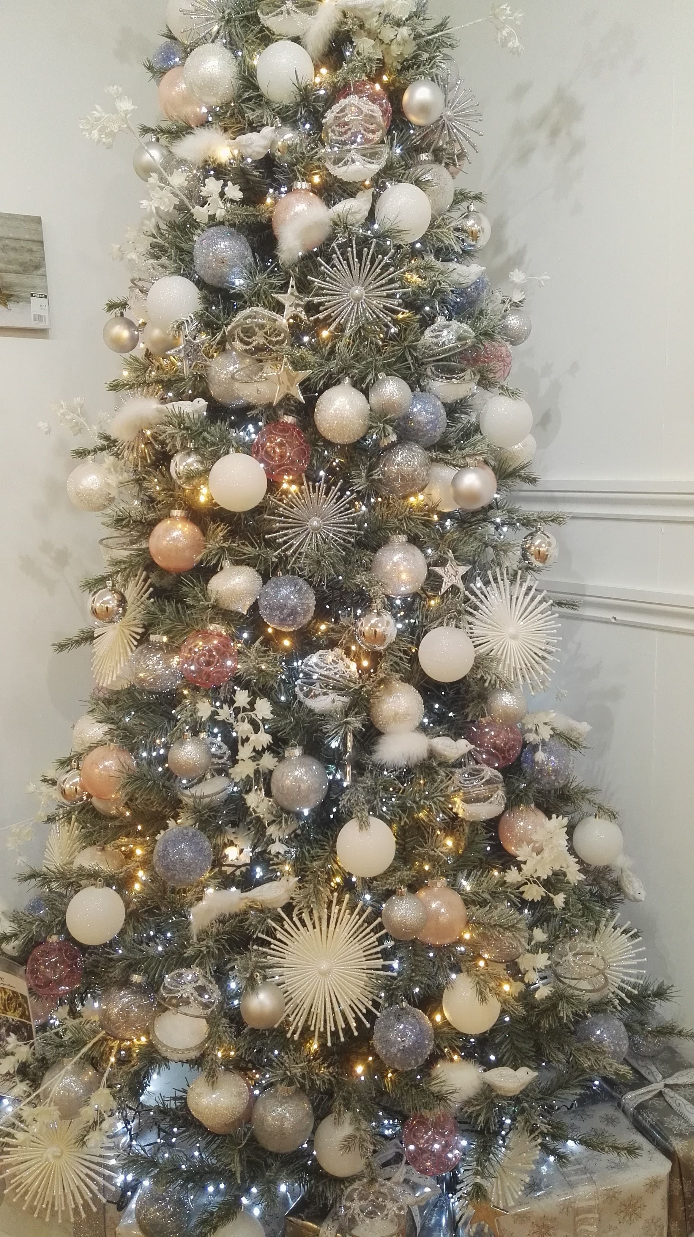 A Sophisticated Tree With Large Starburst White Birds And Baubles Filled Wi Christmas Themes Decorations Christmas Decorations Tree Christmas Tree Decorations
