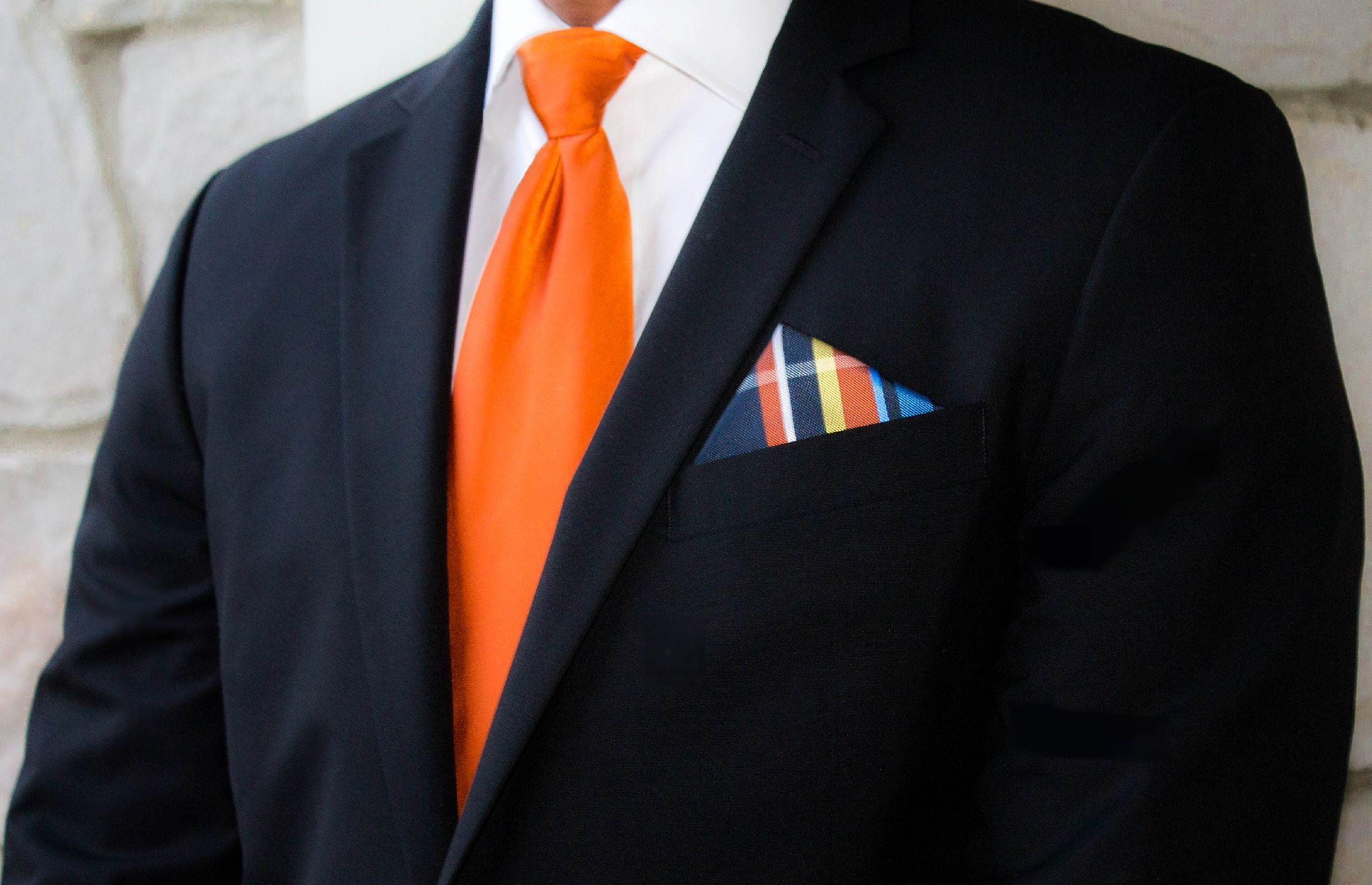 black suit with a bright orange tie suit and tie