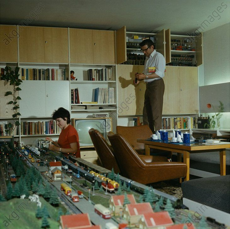 ehepaar beim gemeinsamen hobby einer modelleisenbahn die im wohnzimmer aufgebaut ist ddr um. Black Bedroom Furniture Sets. Home Design Ideas