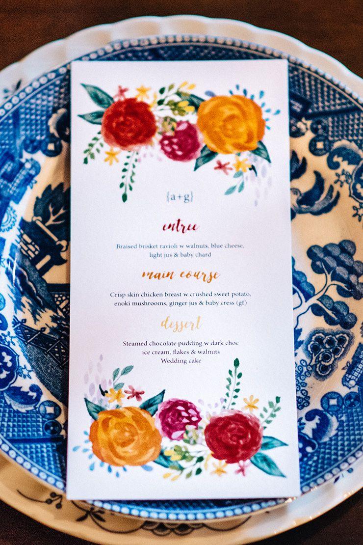Bright orange and red floral wedding menu on blue china | Peppermint Photography