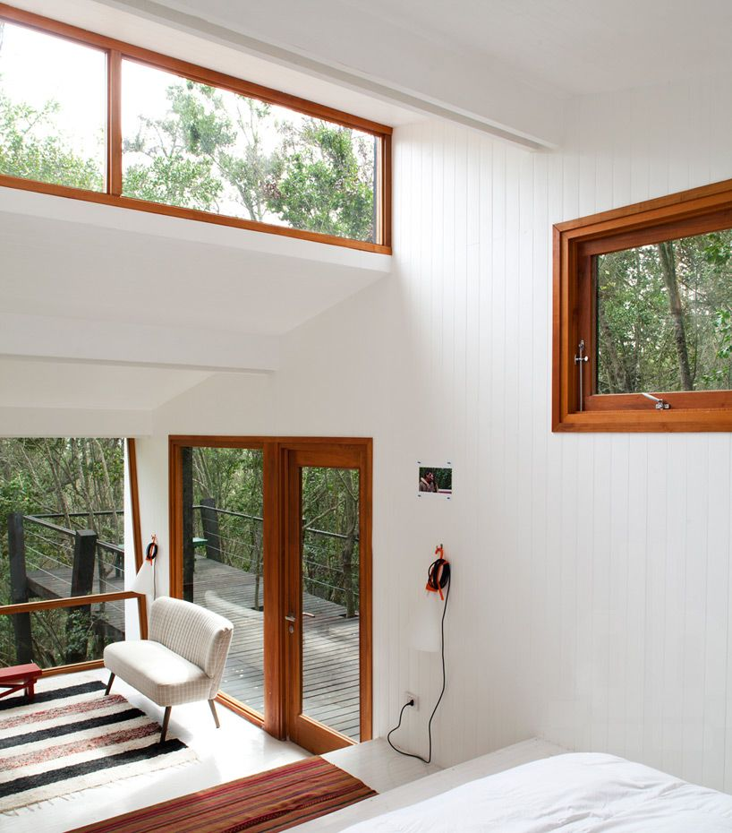 UNarquitectura casa quebrada | white interior with natural wooden framed windows and doors