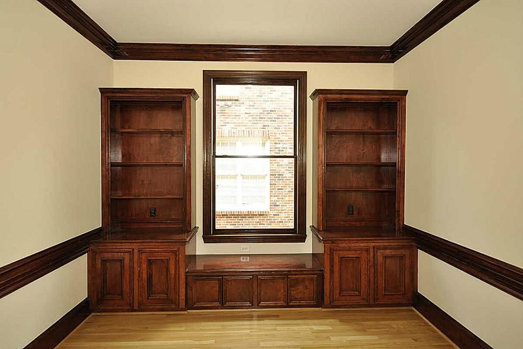 Home Office With Stained Trim And Built In Bookcases