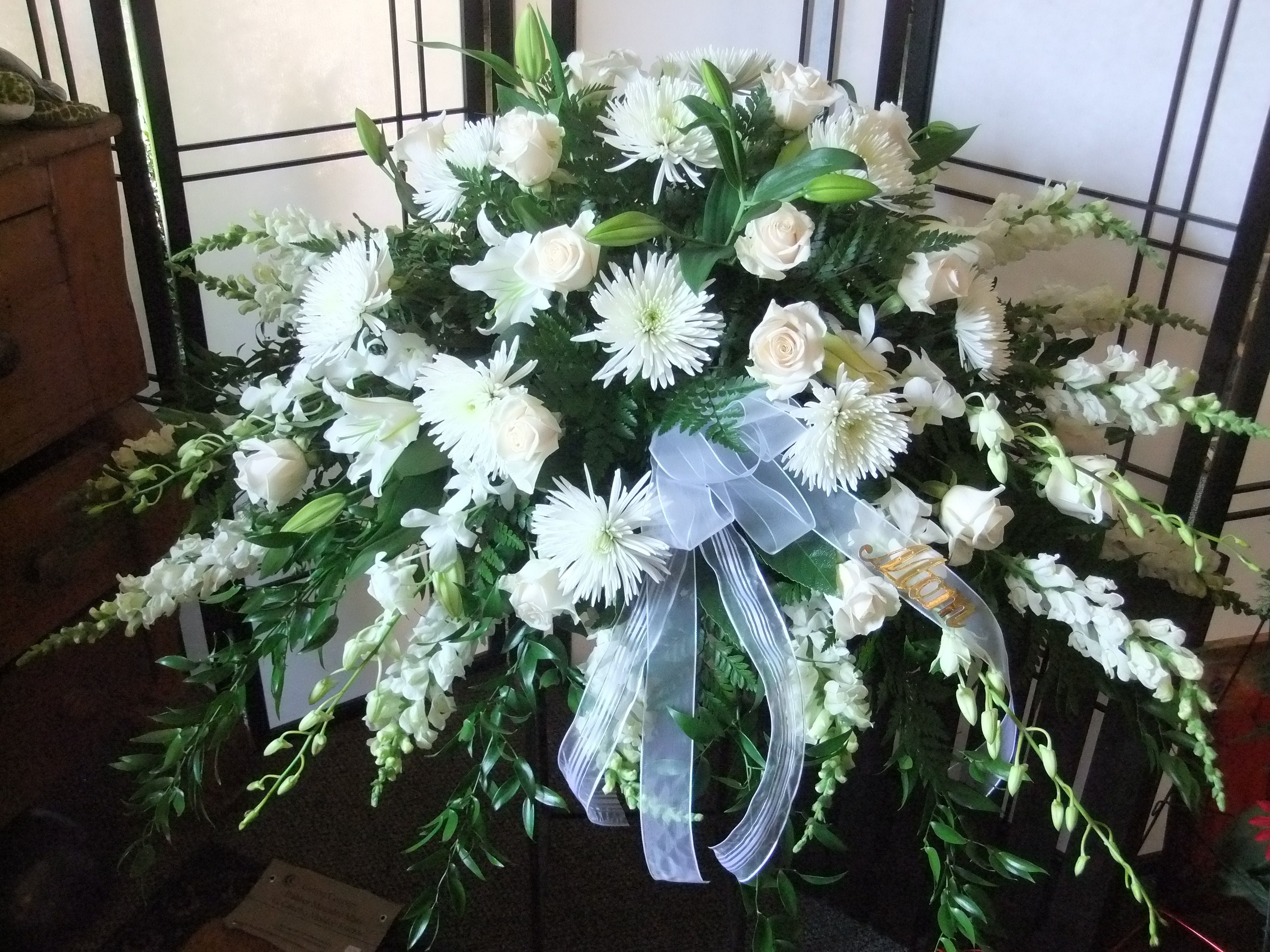 On angels wings casket spray with white glads lilies snaps funeral flowers on angels wings casket spray with white glads lilies snaps dendros izmirmasajfo Images