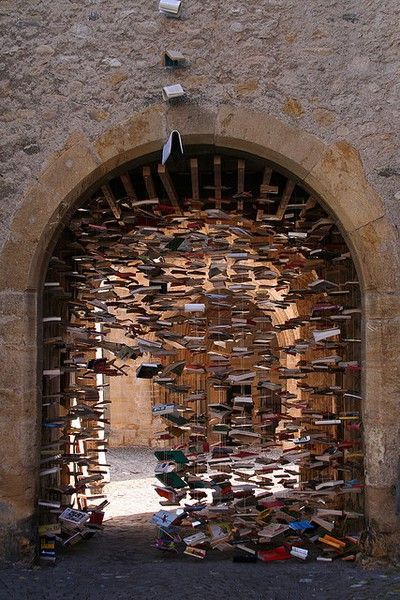 Books Suspended in Archway.  (I cannot locate the photo among the archives of the original posting. Perhaps you can: http://artssake.tumblr.com/archive).