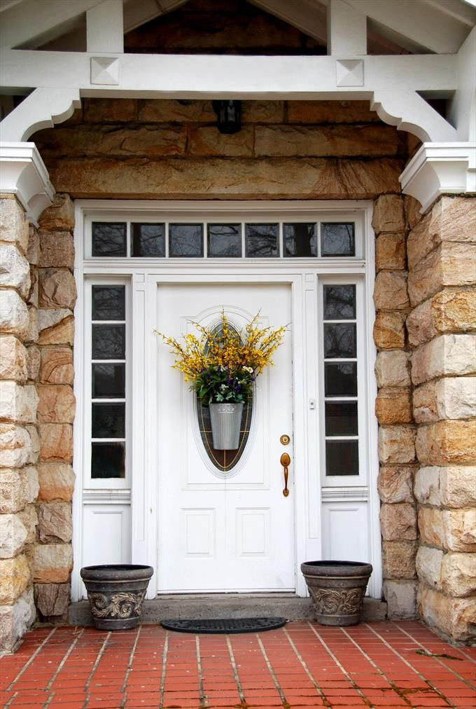 Stone Entrance Featuring White Door W Oval Glass Insert Copper