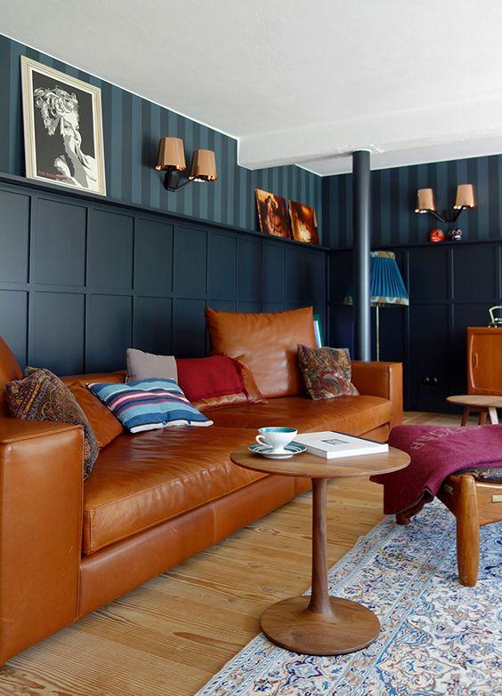Wände in blautönen und ein cognacfarbenes Sofa machen dieses