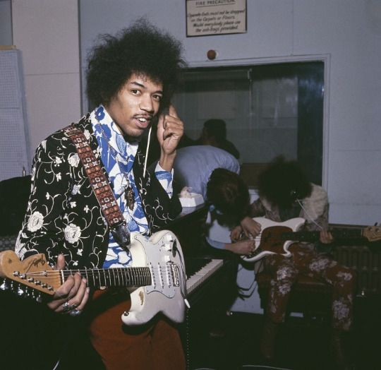 American guitarist Jimi Hendrix of The Jimi Hendrix Experience in a London recording studio, c. October 1967 Background includes bassist Noel Redding and manager Chas Chandler setting up