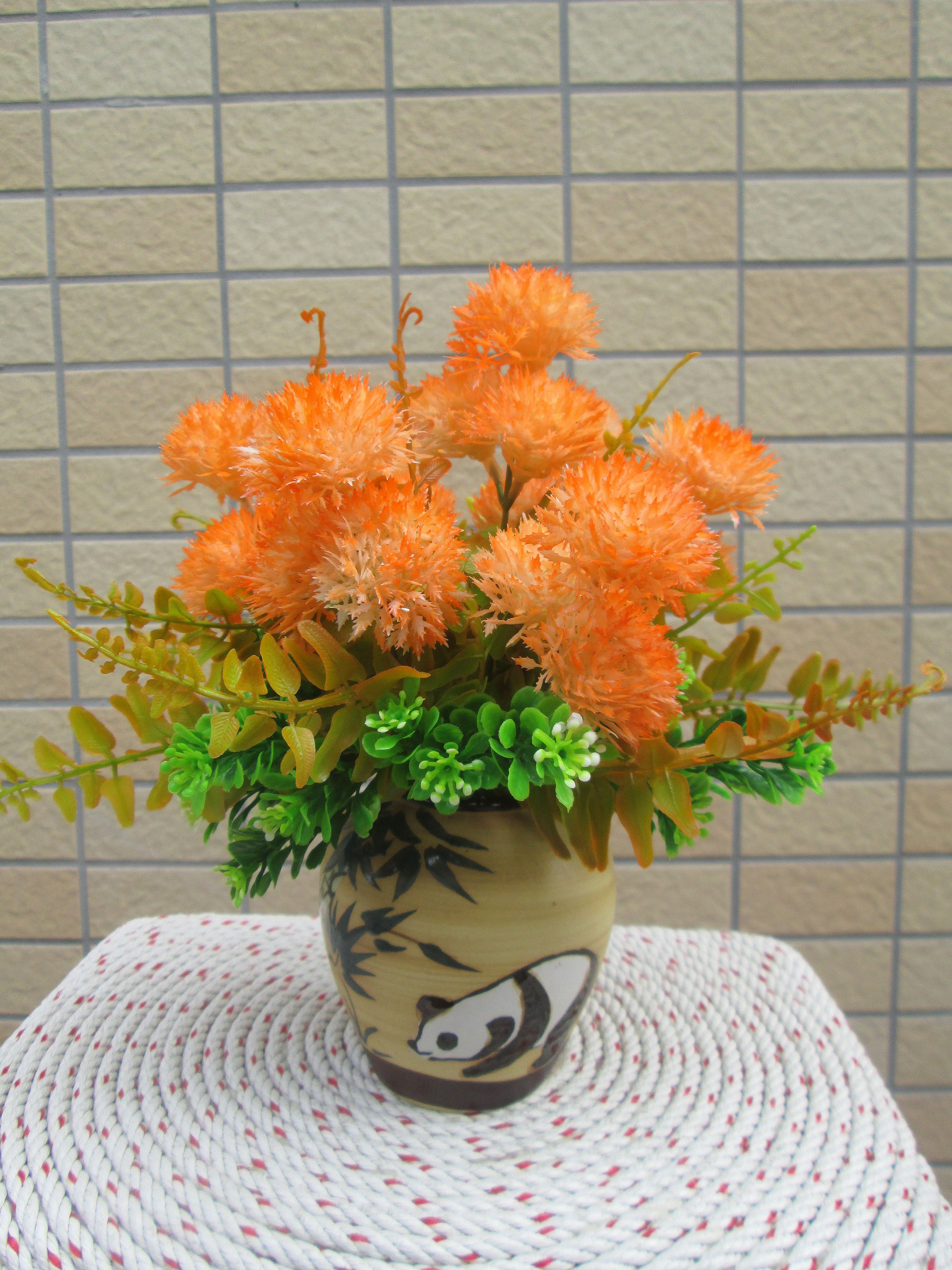 Những bông hoa tròn như quả chôm chôm màu cam kết hợp bình gốm vẽ