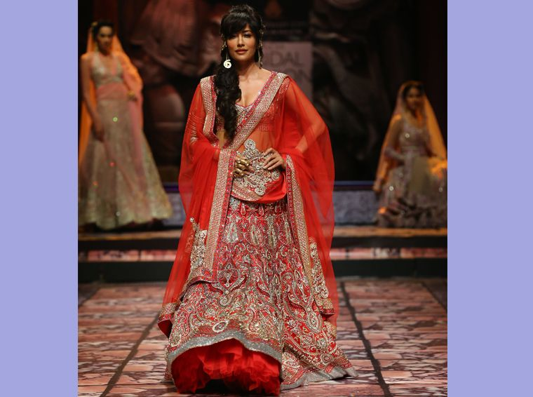 Chitrangada Singh walks the ramp in a red and gold shimmery lehenga from Suneet Varma's collection.