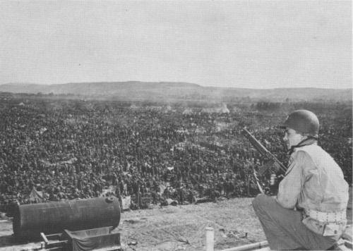 A GI guarding a corner of a German POW camp near Remagen, 25 Apr 1945