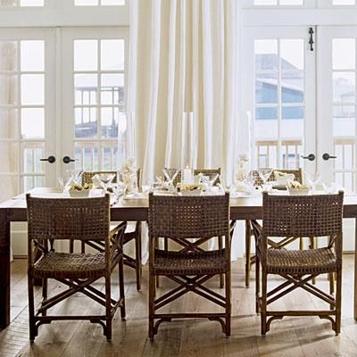 Dining Room Chairs With Brown Wicker Mesh Backing Surround A Dining Room  Table Decorated With White Candles, Glassware And Sea Shells