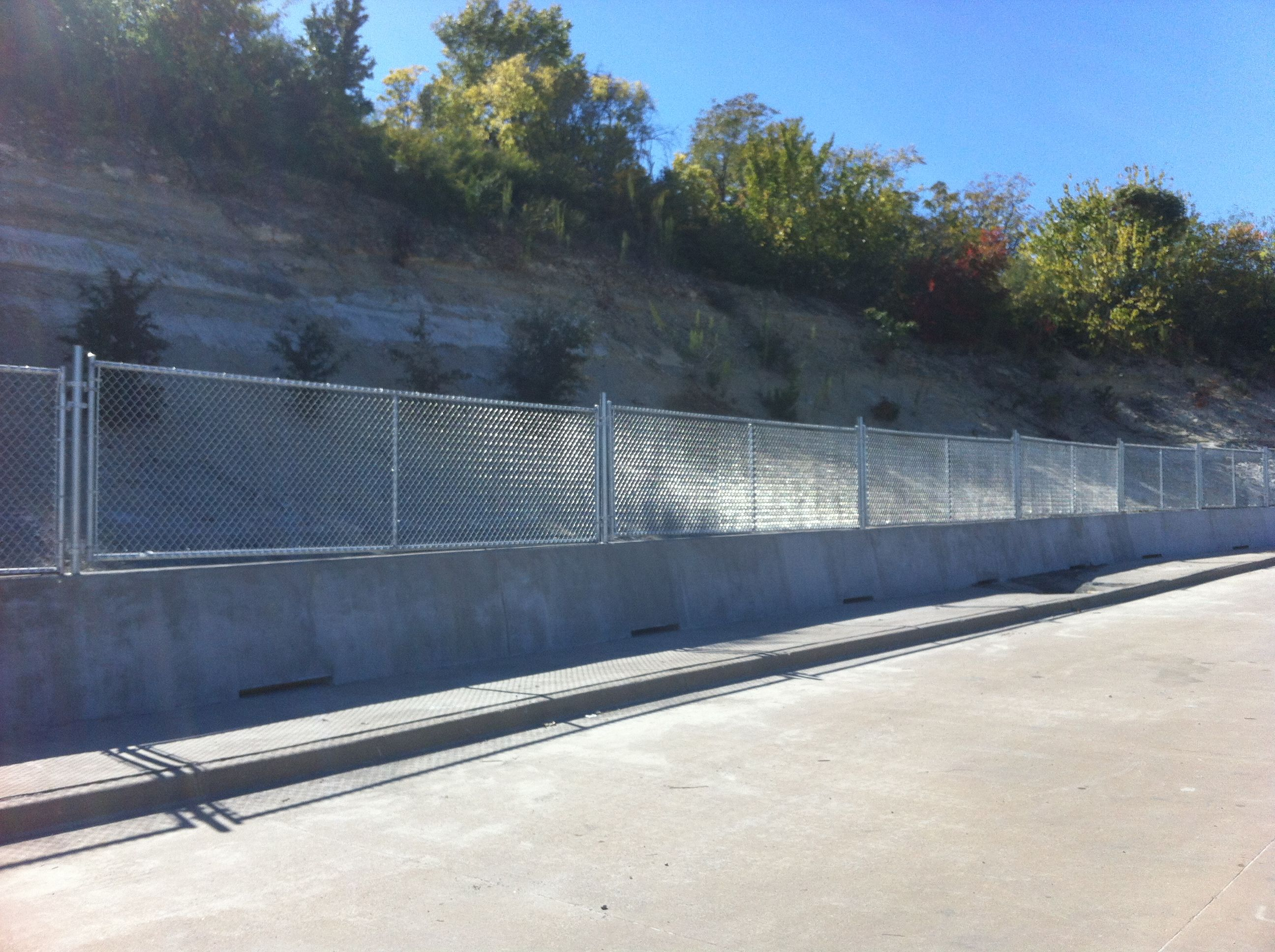 Chain Link Fence On Top Of Concrete Wall Installed By