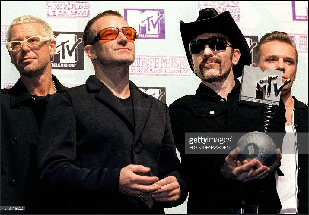 U2 lead-guitarist 'The Edge' (2nd R) holds the MTV 'European Music Award' while the group's lead singer Bono Vox (2nd L) and the other band members look on, after the Irish rock group was awarded he MTV Award for the 'best live performance' category during a ceremony in Rotterdam, 06 November night 1997. / AFP / ANP / ED