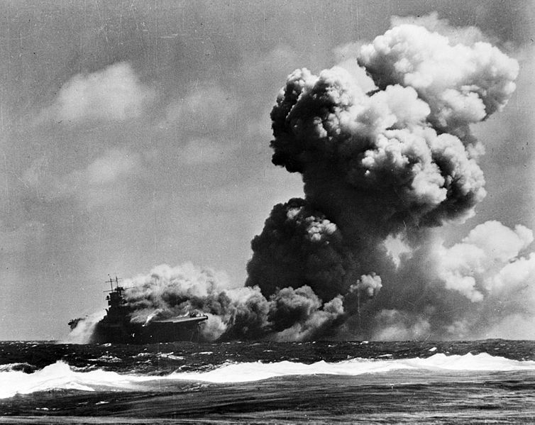 USS Wasp (CV-7) burning after receiving two torpedo hits from the Japanese submarine I-19 while steaming well to the southward of Guadalcanal, 15 September 1942.